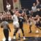 Two girls jump for the tip-off to begin their high school basketball game.