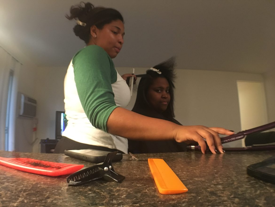 English junior Laurielle Martin works with a hair client. Martin uses social media to promote her business.