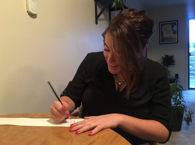 Photo of teacher Dayle McLeod working on classroom decorations at a table.
