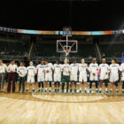 MSU women's basketball team players and coaches lock arms wearing UNITY shirts during national anthem.