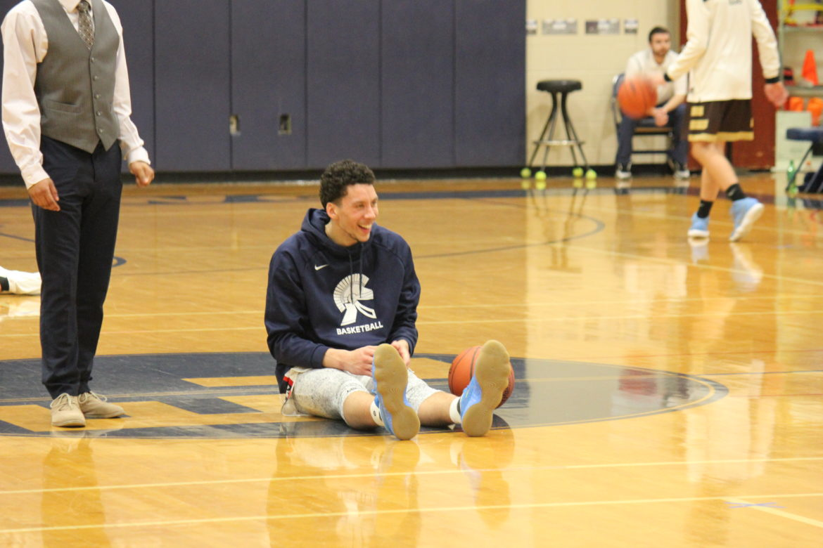East Lansing senior Brandon Johns laughs with his teammates while he stretches before a game.