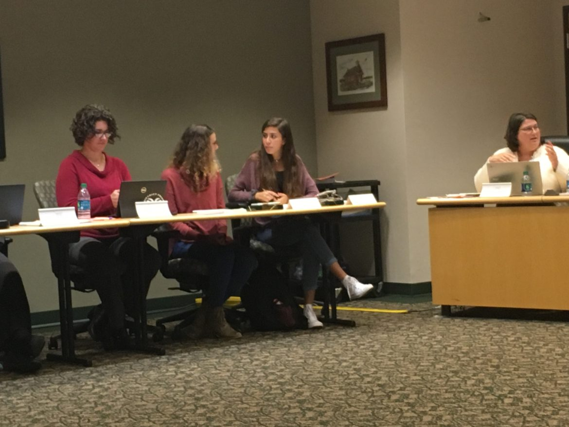 Adele Colson (left) talks to Isabel Abdouch (right) during the first Holt Public Schools Board of Education meeting on Oct. 1. The students serve as advisers to the school board.