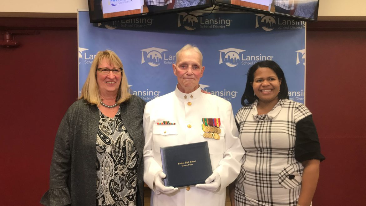 Retired Chief Petty Officer Dann Huisken (center) with Lansing Board of Education President Rachel Lewis (right) and Superintendent Caamal Canul (left) after receiving his high school diploma.