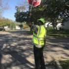 Alfred Anderson, a cross guard at Attwood Elementary School, stops traffic to let students cross the street.