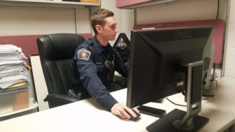 East Lansing Police Officer Jordan Woodruff sits at a computer and composes a tweet.