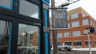 Blue Owl Coffee logo on a sign in front of the REO Town location.