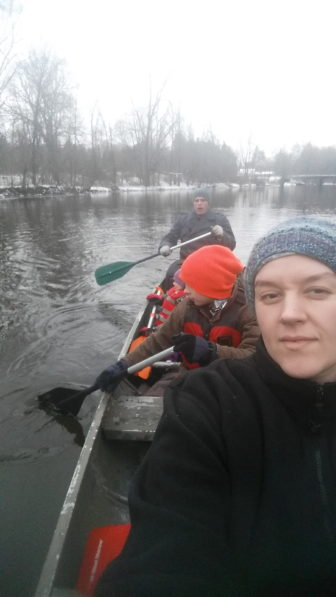 A white female taking a selfie of her family and herself while kayaking on the river.