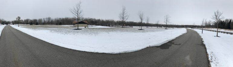 A panorama of Hawk Island paved trails with snow in the background.