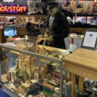 """Photo of the Dicker and Deal store, with lots of assorted items for sale and a large, glowing sign reading """"cool stuff"""" in the background"""