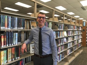 Scott Duimstra who is dressed in a blue button down shirt with a black tie leans on the shelves of books.
