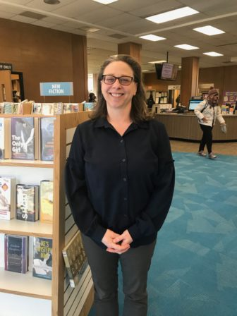 Michele Brussow smiling while standing in the Downtown Lansing library.