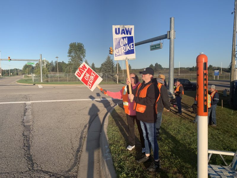 Kathy Berry and daughter Kellie Bowden stand outside General Motors Co.'s Lansing Delta Township Assembly as part of a UAW picket line. The nearly monthlong strike is leading workers to spend less, impacting the local economy.