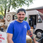 man in blue shirt stands by food truck