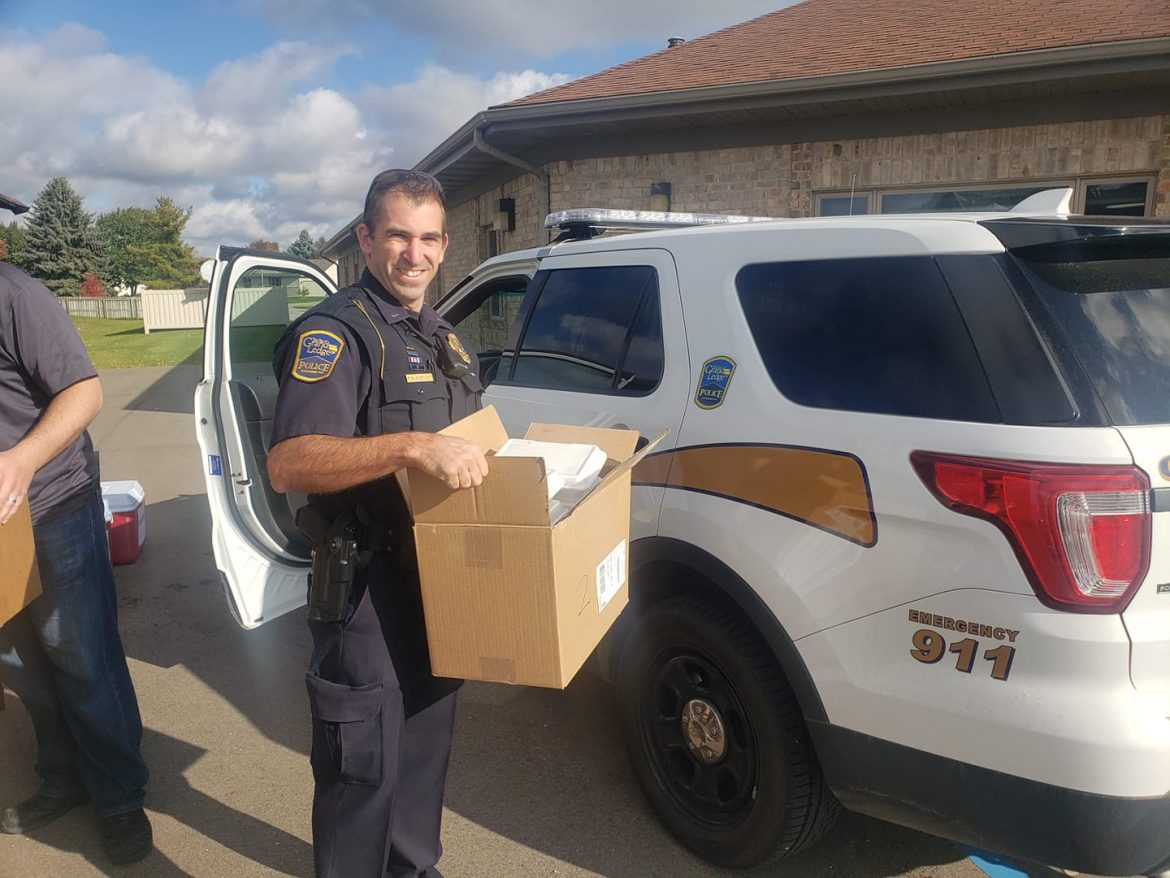 An off-duty Grand Ledge police officer in uniform delivers lunch to those who couldn't make it out to Bye Financial Group. Food deliveries were made to donors throughout the entire event. Photo used with permission. Photo Credit: Grand Ledge Police Department