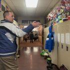 A man gesturing towards lockers