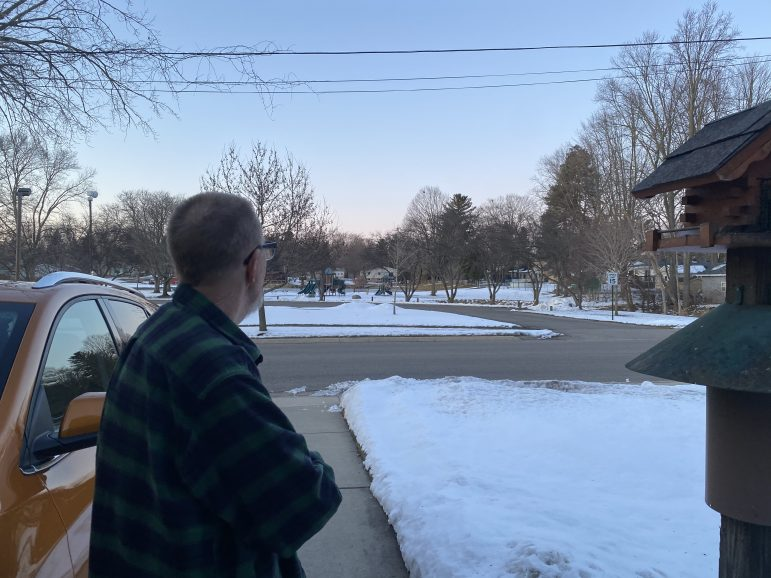 Roger Bauer looks at the park across the street, covered in snow.