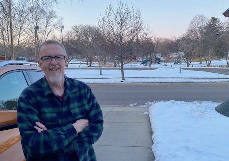 Roger Bauer stands in his driveway, across the street from a city park, smiling.