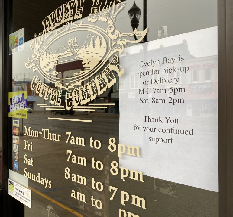 Sign outside of cafe with hour change and a thank for continued support.