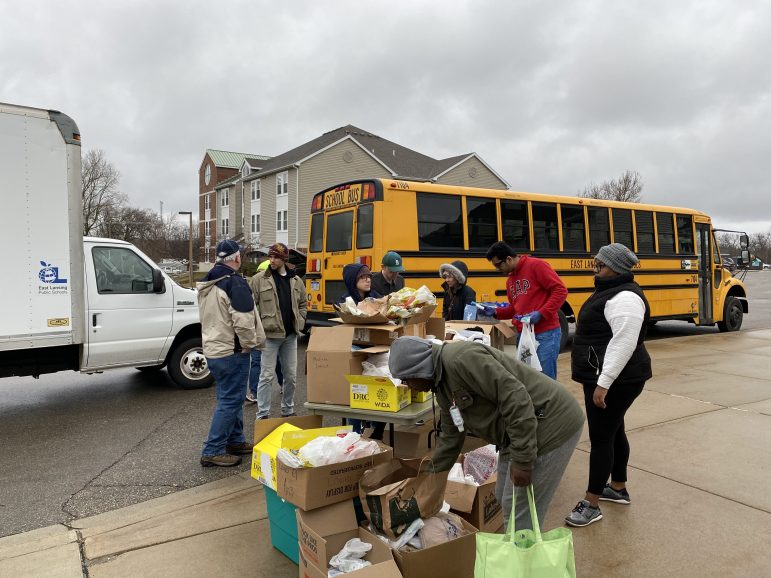 Teachers and volunteers hand out free meals for parents at 1855 Community Center. Packages include grab-and-go meals, snacks, and books.