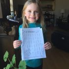 First grade girl holds learning packet.