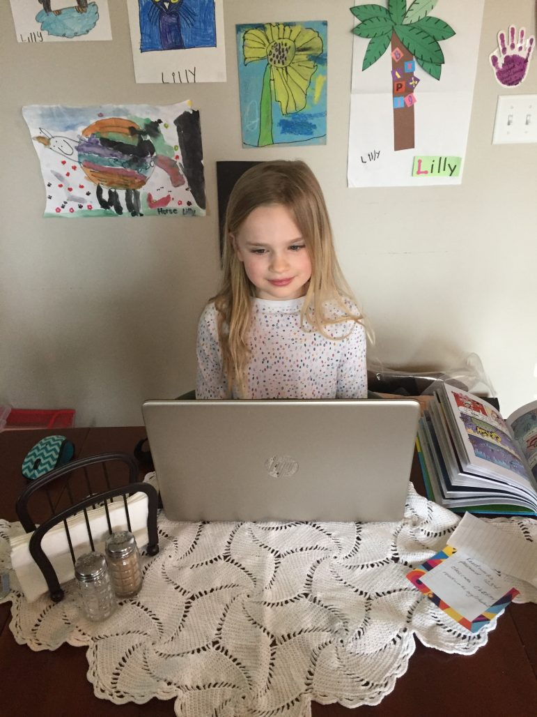 First grade girl types on a laptop.