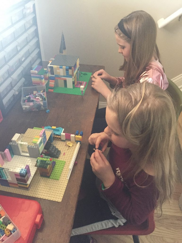 Two young girls build with LEGOs.