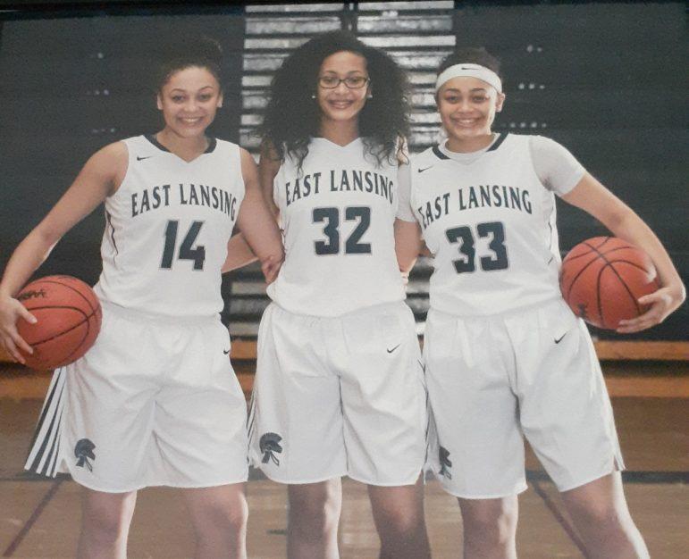 Three high school basketball players in uniform.