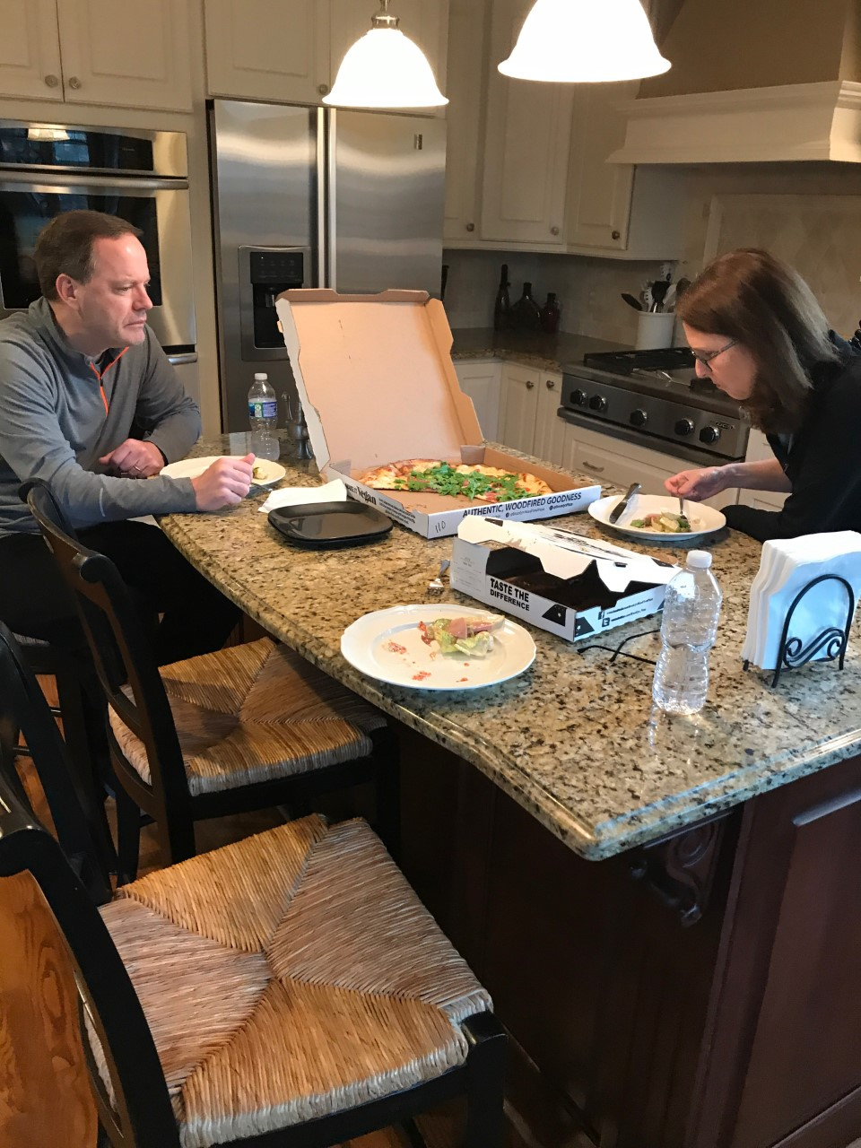 Family eats pizza at home