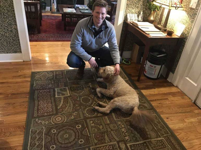 Manager of the inn plays with his dog