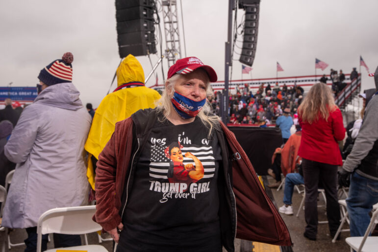 """A woman wears a shirt that says """"Yes I'm a Trump Girl, get over it"""" at a political rally for President Donald Trump at the Capital Region International Airport in Lansing on Tuesday, Oct. 27."""
