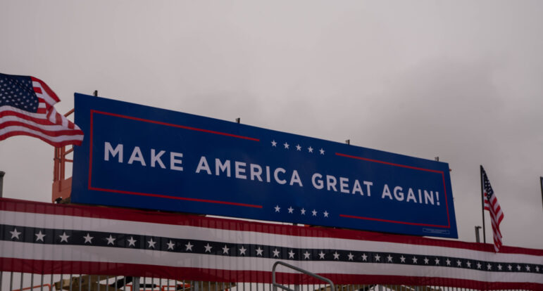 """A """"Make America Great Again"""" sign was positioned above bleachers at a political rally for President Donald Trump at the Capital Region International Airport in Lansing on Tuesday, Oct. 27, 2020."""