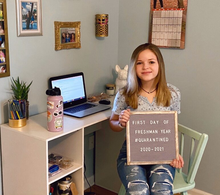Jordan Fields, a freshman at Grand Ledge High School, sits at her desk at home for a photo marking the first day of school. Grand Ledge students are spending the first trimester online.