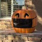 Pumpkin on a porch wearing a COVID-19 mask