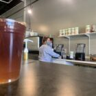 An employee works beyond the counter preparing a beverage at Central Lansing Nutrition.