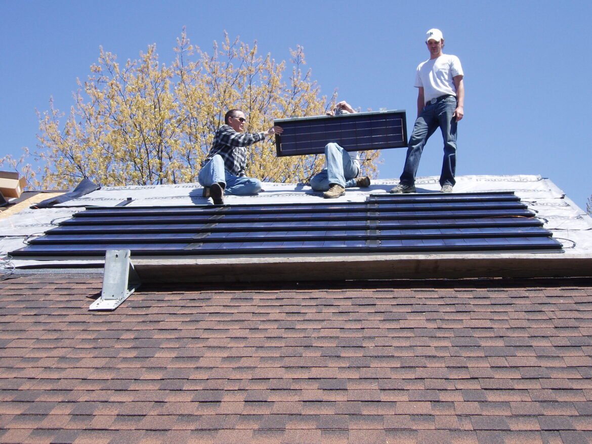 Installation of the roof-integrated solar panels on John Sarver's East Lansing home in 2010. These were the only panels he used until 2019 when he added additional traditional style panels.