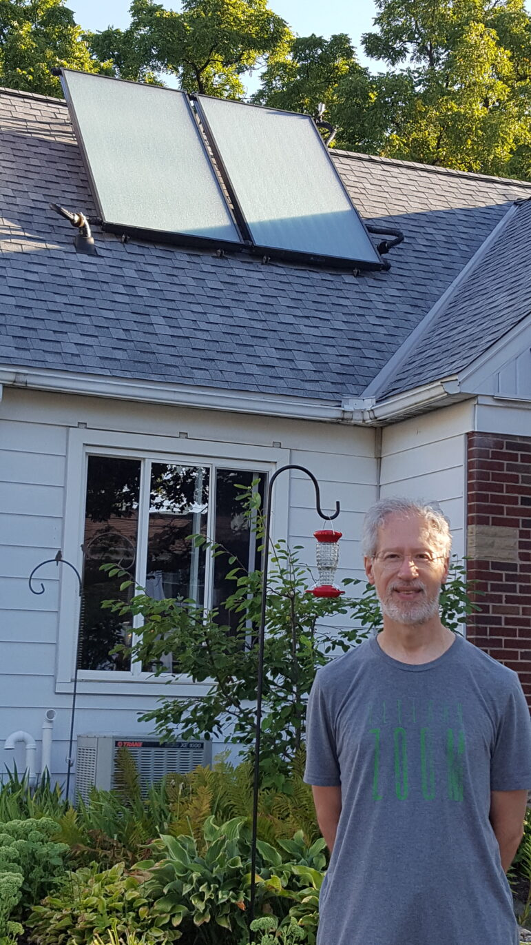 Bob Synk and the solar panels being installed on the roof of his home in Grand Rapids this year.