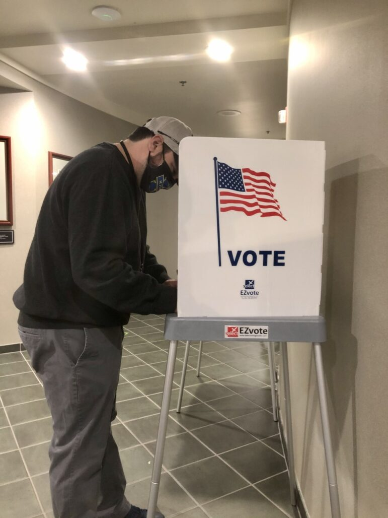 At the Delhi Township Clerk's Office, Holt resident Travis Maki votes while wearing a mask, social distancing, and using his own pen he brought from home. Travis Maki is wearing a black crewneck, grey jeans, and a tan hat.