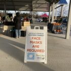 A sign at the Meridian Farmers Market in Ingham County reminds shoppers to mask up.