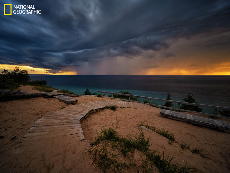 Lake Michigan–As the sun sets, a curtain of rain descends from storm clouds near Sleeping Bear Dunes National Lakeshore on the northeastern coast of Lake Michigan. Of the five Great Lakes, only Lake Michigan lies entirely within the United States. (Keith Ladzinski/National Geographic)