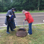 Researchers Becca Ives and Nishita D'Souza lower a container into a manhole to sample wastewater at Michigan State University.