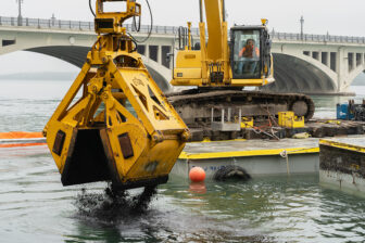 An excavator drops activated carbon into the Detroit River.