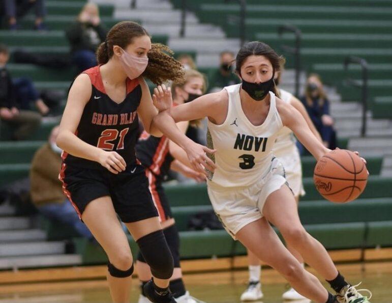 Eva Khalil playing basketball against Grand Blanc.