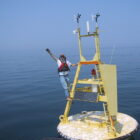 National Oceanic and Atmospheric Administration scientist Mike McCormick, co-author of a study on Lake Michigan's deep water temperatures, stands on an instrument buoy in southern Lake Michigan.