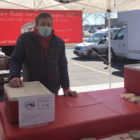 Man stands at farmers market table.