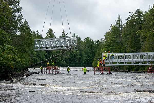 Park workers use a helicopter to install a new pedestrian bridge at Tahquamenon Falls State Park.