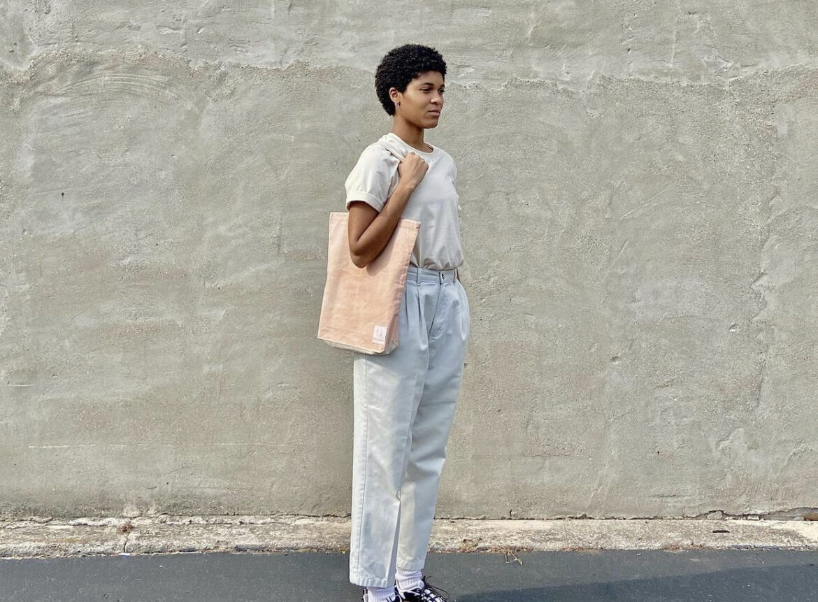 Owner of the small business carries a light pink tote bag.